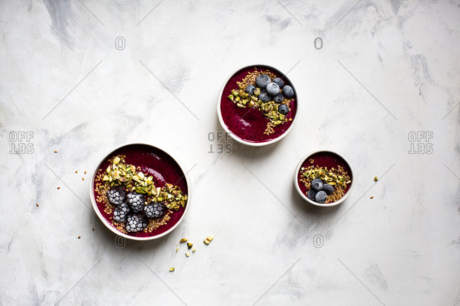 Smoothie bowls topped with pistachios and frozen berries