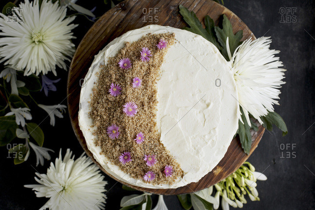 Marzipan Almond Cake with a Orange Blossom Mascarpone Frosting on a wooden pedestal, served with Rose wine