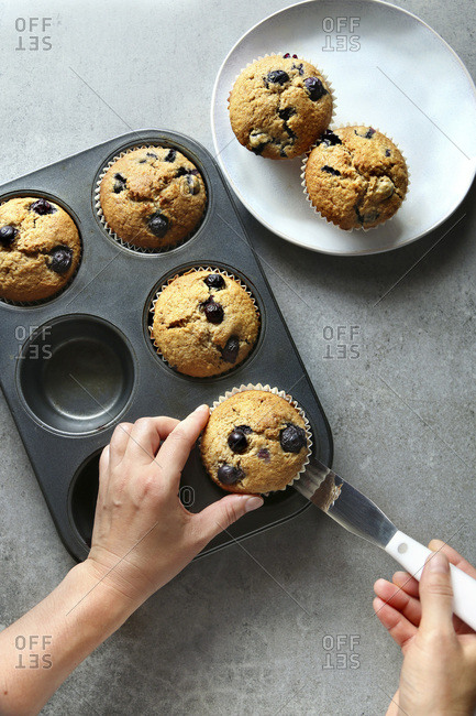 Hands removing a blueberry muffin from a baking pan