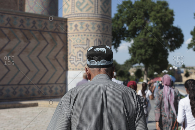 Samarkand, Uzbekistan - May 29, 2016: Man with traditional hat walking in Samarkand