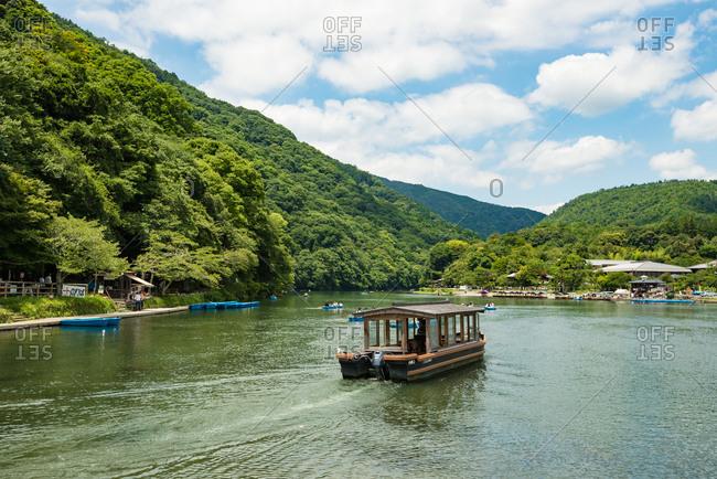 KYOTO, JAPAN - JULY 18, 2016: People sailing boats at Arashiyama district, Kyoto