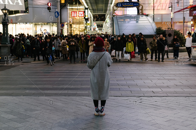 Osaka, JAPAN - February 11, 2017: Back view of a young woman waiting for green traffic light