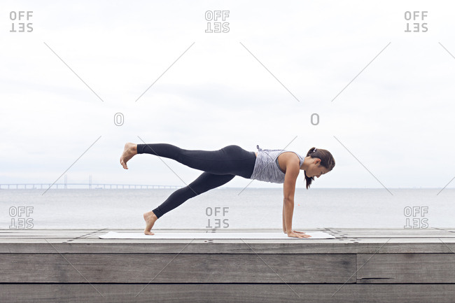 Woman on a seawall in a yoga plank pose
