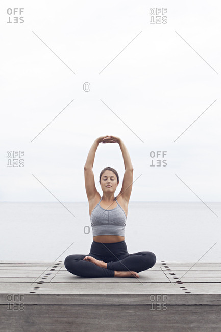 Woman sitting in a yoga position with her arms raised over her head