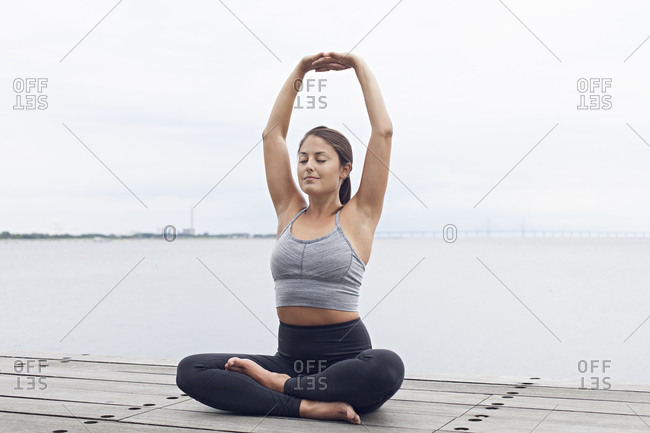 Woman sitting with her arms raised above her head in a yoga pose