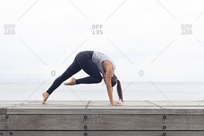 Woman in a bent yoga pose with one leg raised