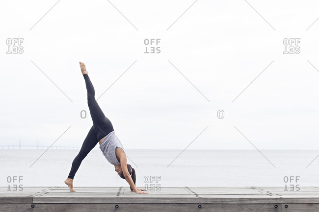 Woman bent forward in a yoga pose with one leg raised straight outward