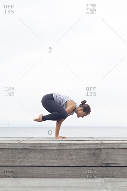 Woman in a crow pose balancing on a seawall