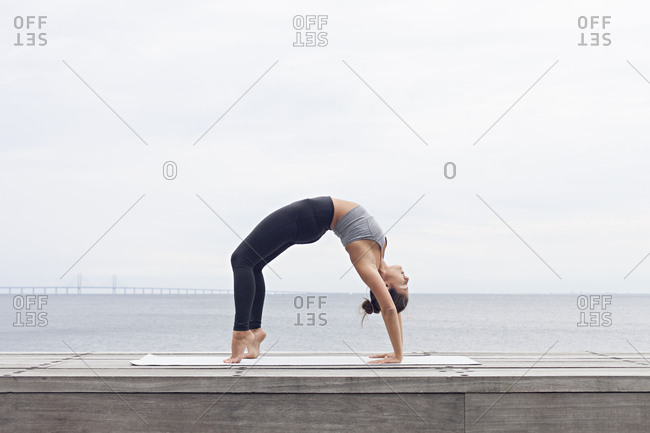Woman bending backward in a wheel yoga pose beside a bay
