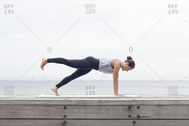 Woman in a yoga plank position on a wall beside a bay