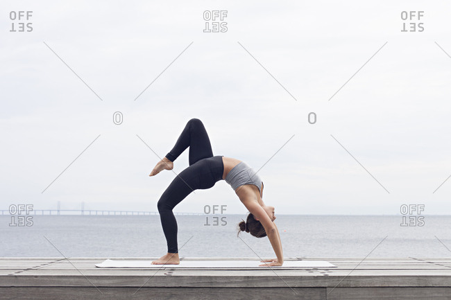 Woman bending backward in a wheel yoga pose with one leg bent