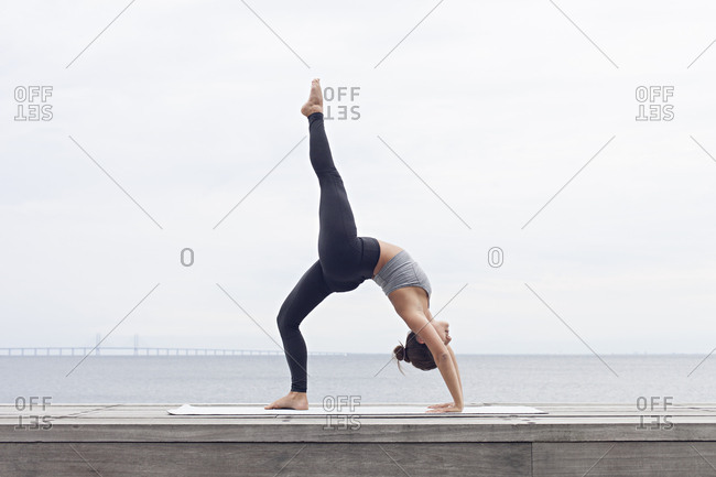 Woman bending backward in a wheel yoga pose with one leg raised in the air