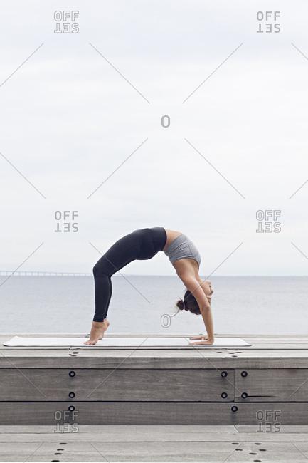 Woman bending backward in a wheel yoga pose on a seawall