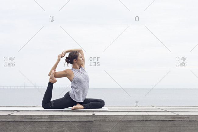 Woman in a seated yoga position holding her foot behind her head