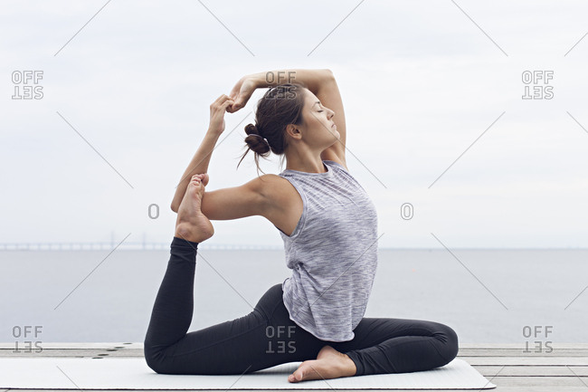Woman sitting in a yoga position holding her foot behind her head
