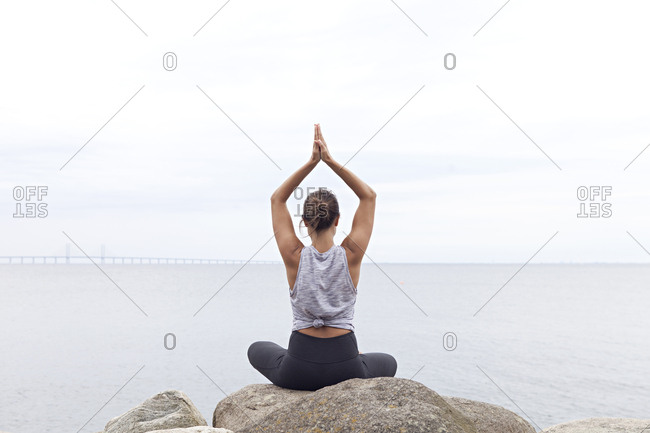 Woman in a seated yoga position with her arms folded above her head