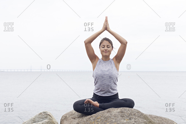 Woman seated in a lotus yoga position on rocks beside a bay