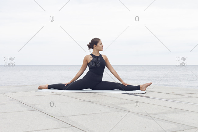 Woman in a split yoga position on a seawall