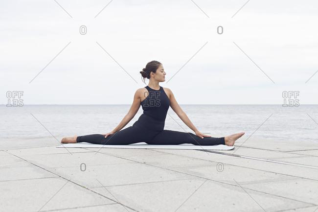 Woman in a split yoga position on a seawall