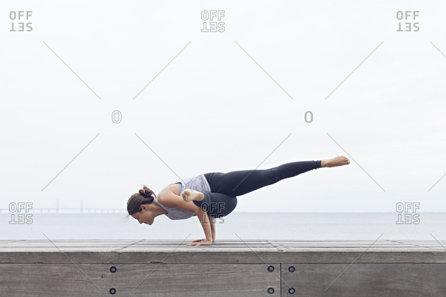 Woman balancing on her palms in a yoga position