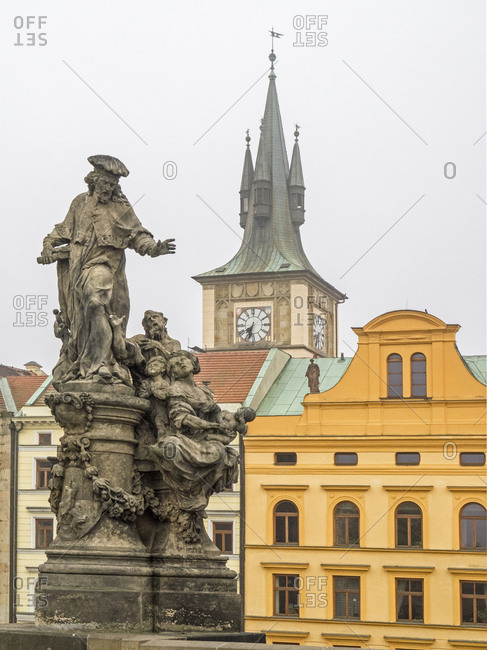 Czech Republic, Prague. Statue on the Charles bridge with the clock tower behind. In 1878, another floor and clock tower was added to the Old town water tower