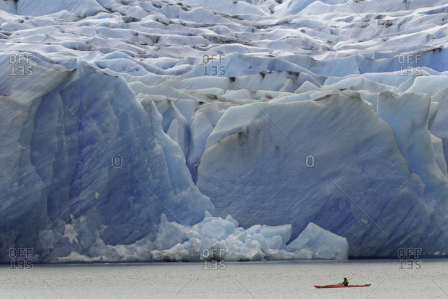 South America, Chile - January 31, 2016: Kayaker exploring Grey Lake and massive Grey Glacier, Torres del Paine National Park, Chile, Patagonia