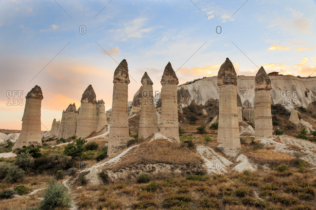 Turkey, Anatolia, Cappadocia, Goreme. Fairy Chimneys and field landscapes in the Red Valley, often referred to as 'Love Valley' Goreme National Park, UNESCO World Heritage Site