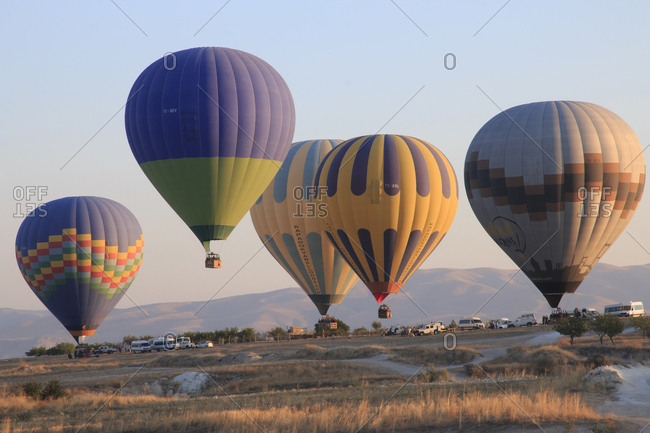 Turkey - September 28, 2015: Turkey, Anatolia, Cappadocia, Goreme. Hot air balloons at lift-off, preparing to fly above rock formations and field landscapes in the Goreme National Park, UNESCO World Heritage Site