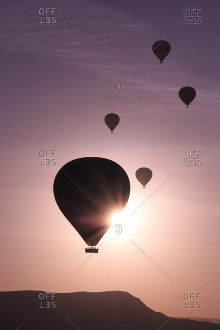 Turkey, Anatolia, Cappadocia, Goreme. Hot air balloons flying above rock formations and field landscapes in the Goreme National Park, UNESCO World Heritage Site