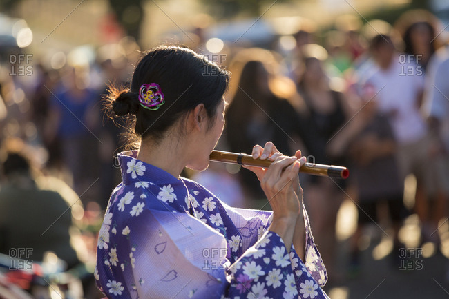 USA, Washington State, Seattle. Chinese New Year celebration in Seattle's 'International District', traditional home of the city's Asian community. Woman playing flute