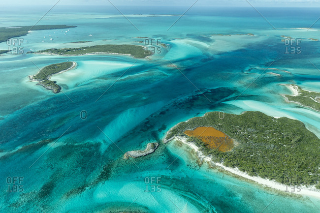 Aerial photo looking down at the clear tropical water and islands in the Exuma Chain of islands the Bahamas near Staniel Cay