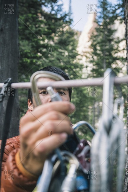 Young mountain climber removing harness from rack in Idaho