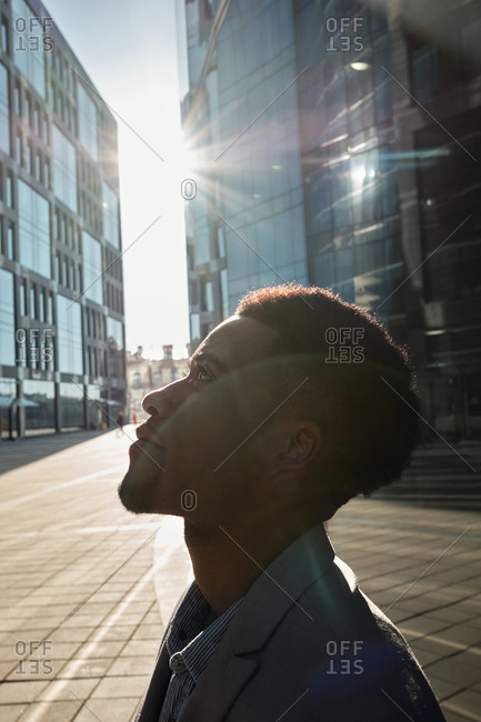 Profile view of young attractive African American standing against modern office buildings, looking up and smiling on sunny afternoon, lens flare