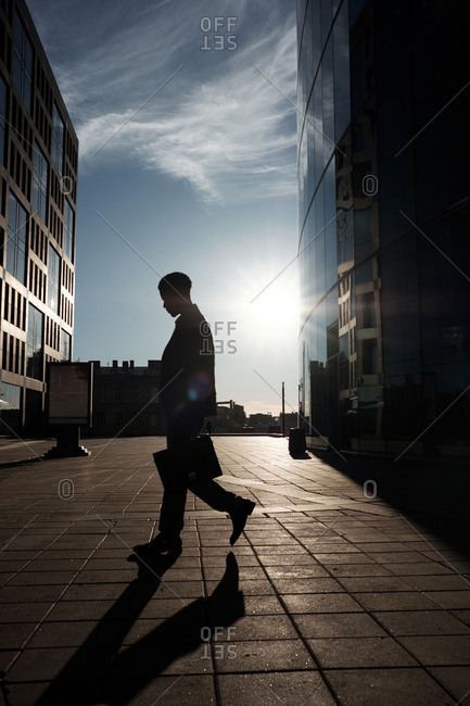 Working from dawn to dusk. Silhouette of male office worker with case going home after hard day at work, modern business centers seen behind him