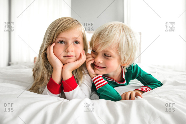 Little boy and little girl have fun in bedroom wearing Christmas pajamas