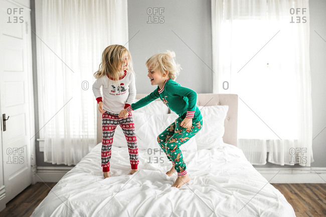 Little boy and little girl jump on the bed wearing Christmas pajamas
