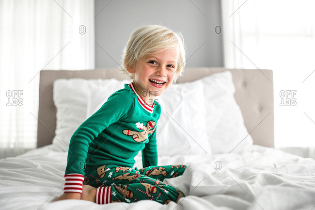 Little boy smiles in bedroom wearing Christmas pajamas