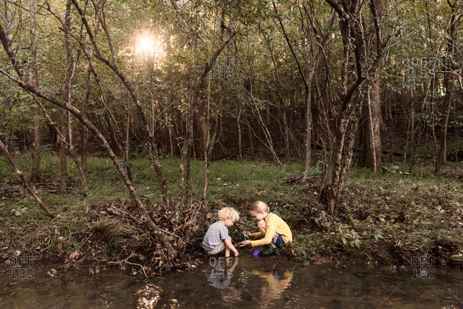 Two kids playing in a creek