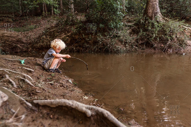 Little boy playing in a creek