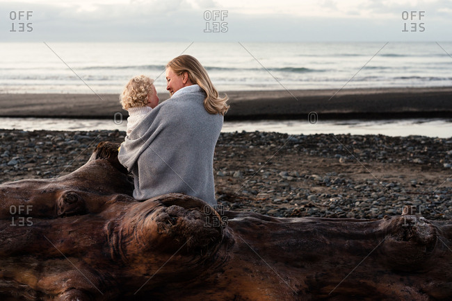 Mother gazing at toddler while cuddling on a log on a beach