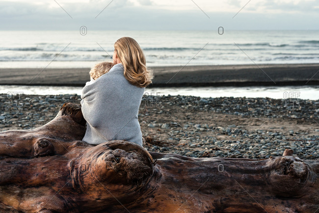 Mother cuddling with toddler on a log on a beach