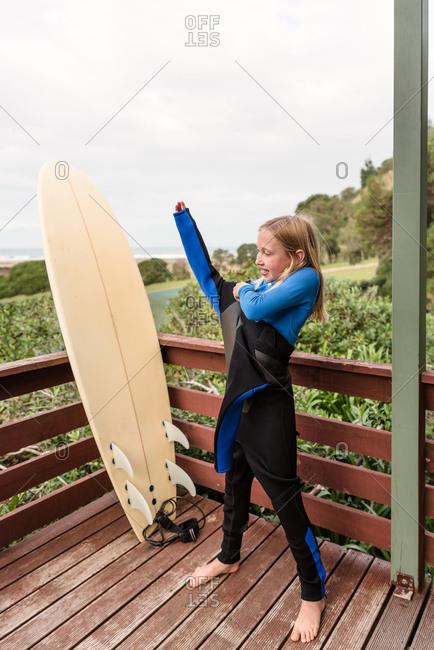 Girl dressing in wetsuit beside a surfboard