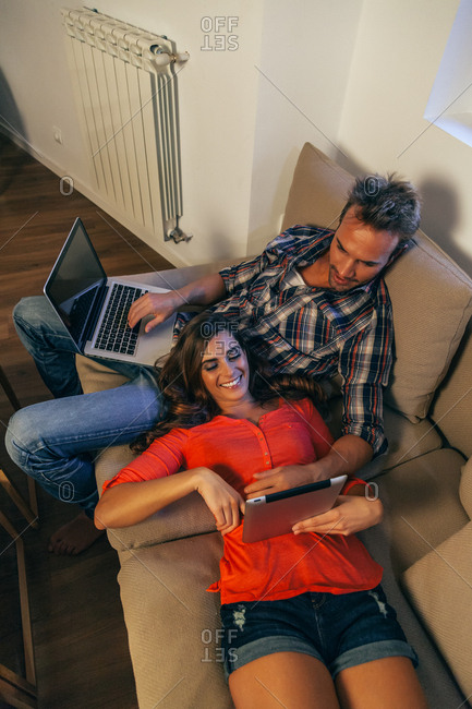 Couple Using a Digital Tablet and a Laptop While Relaxing on a Couch