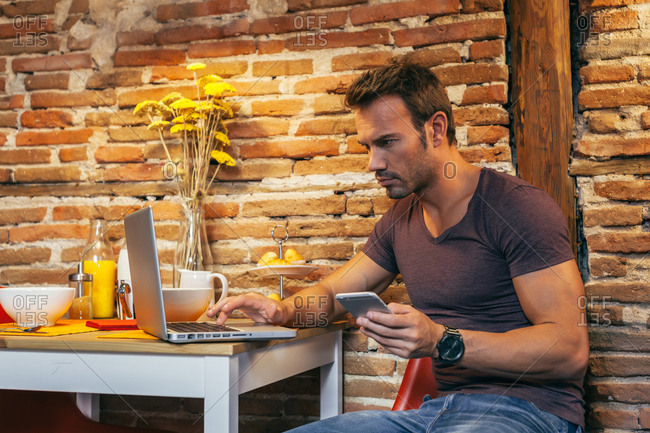 Man Working at Home with a Laptop and Mobile Phone Before Having Breakfast