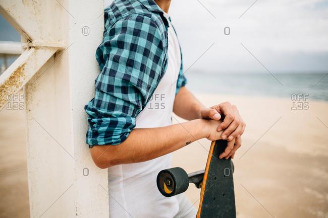 Man in summer apparel holding skateboard on sandy beach.