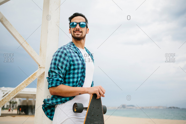 Handsome bearded man in summer outfit standing on the shore with skateboard and smiling.