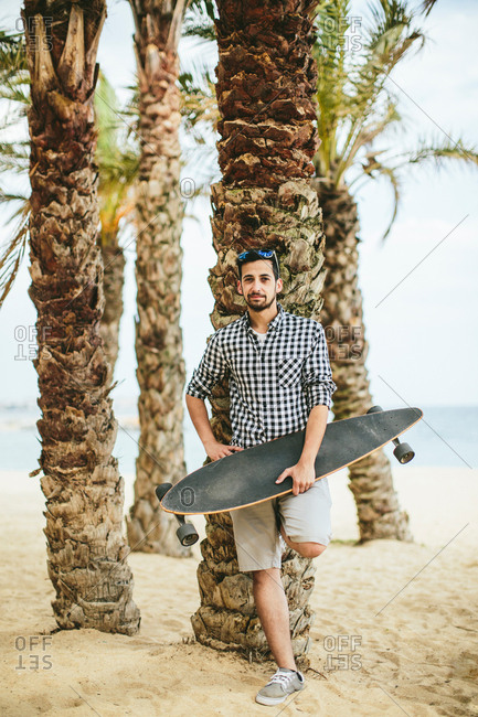 Man in summer apparel with a long board