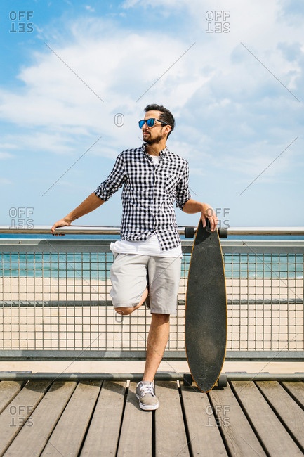 Man in summer apparel standing near skateboard and leaning on fence.