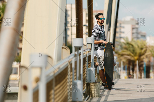 Man in summer outfit standing with skateboard and leaning on bridge fence.