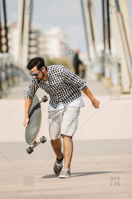 Man in summer apparel skating in park lot.